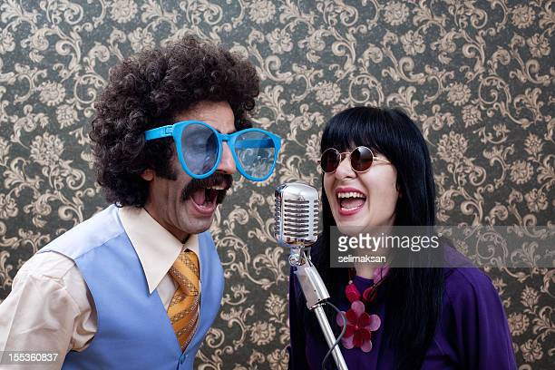 Two friends in seventies style singing on old fashioned microphone