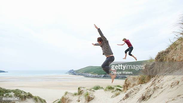 Two friends jump from sand dunes at beach.