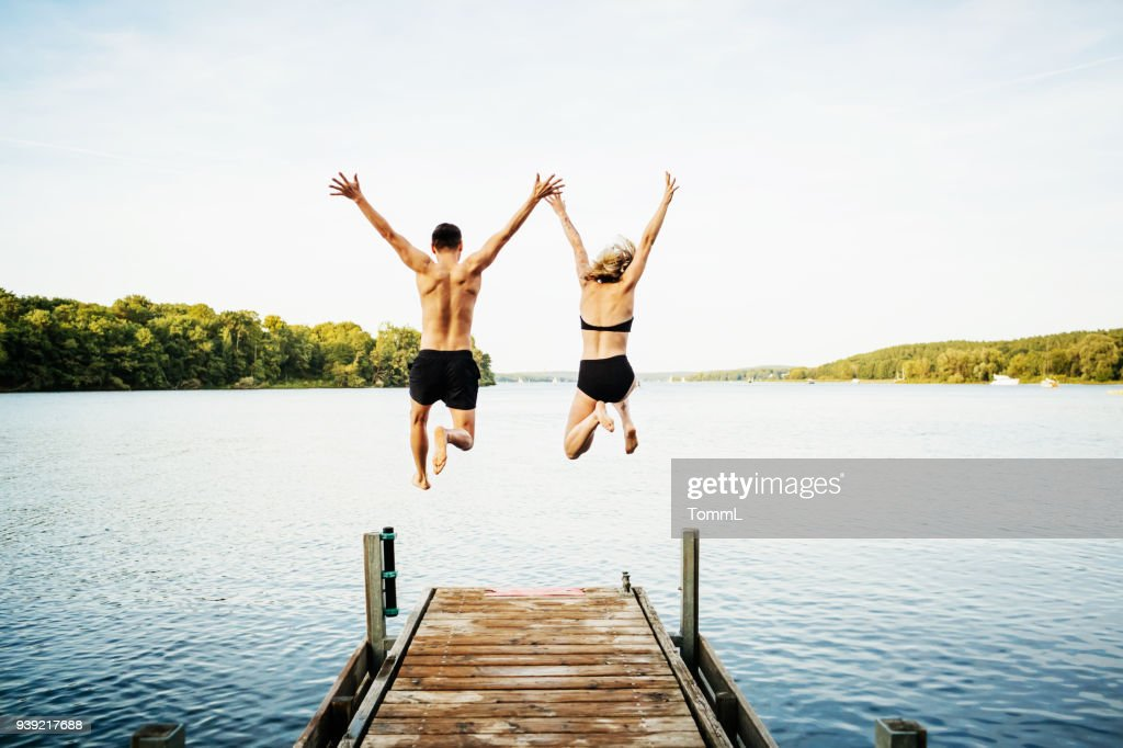 Two Friends Jumping Off Jetty At Lake Together : Stock Photo