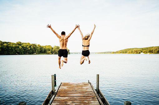 Two Friends Jumping Off Jetty At Lake Together 939217688