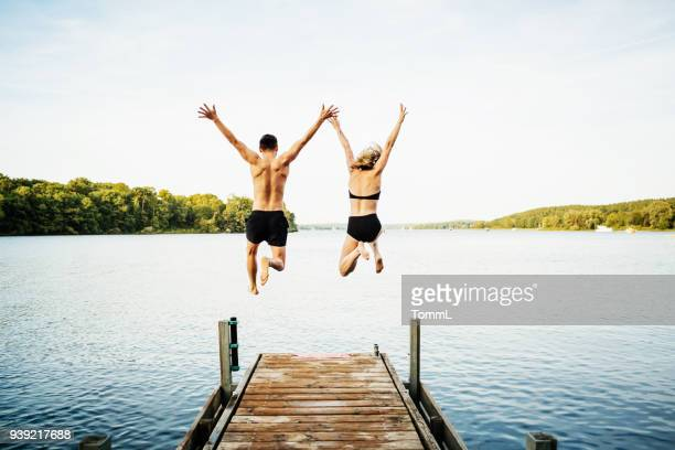 two friends jumping off jetty at lake together - libertà foto e immagini stock