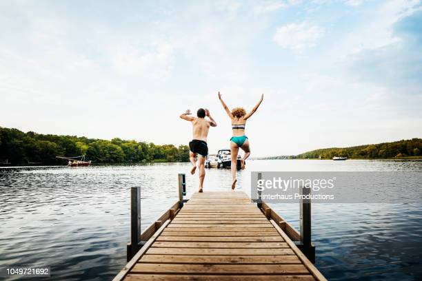Two Friends Jumping Off Pier Together