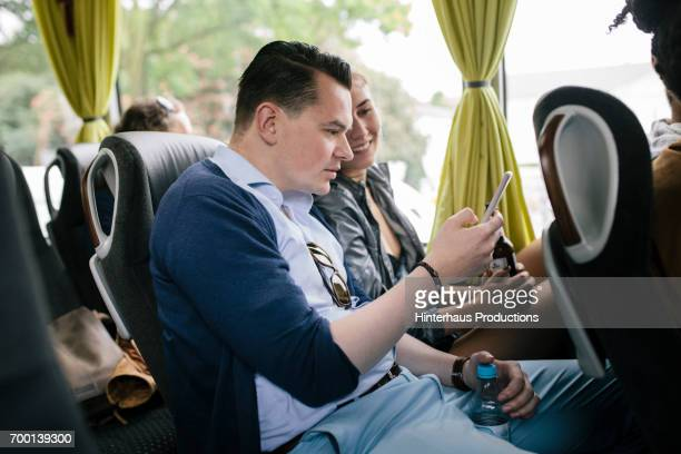 Two Friends Killing Time While Travelling Together On A Bus
