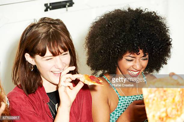Two friends laughing and eating pizza.
