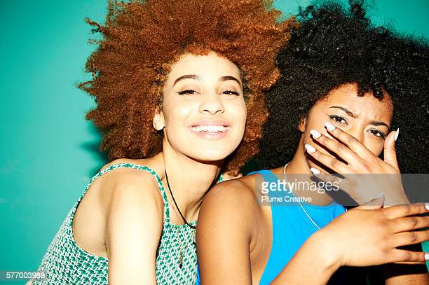 Two friends laughing at party.