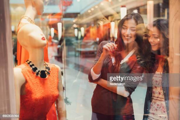 Deux amis en regardant une robe dans un magasin de vêtements