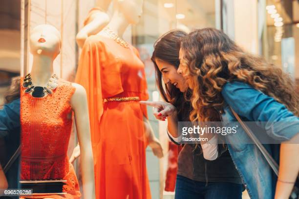 two friends looking at a dress in a clothing store - orange dress stock pictures, royalty-free photos & images