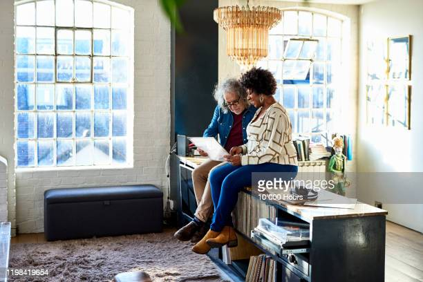 two friends looking at records in loft apartment - carefree stock pictures, royalty-free photos & images