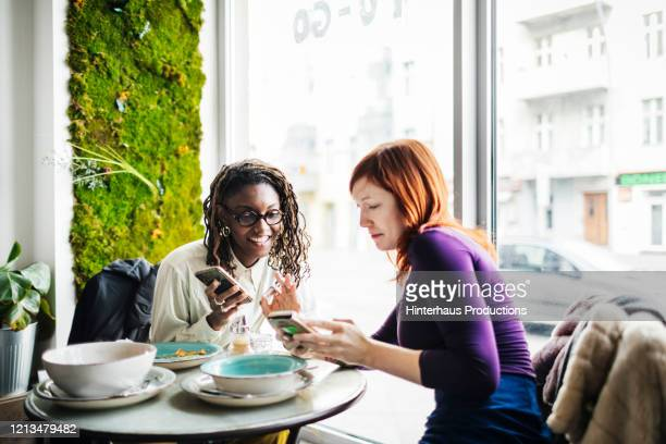 two friends looking at smartphones in cafe - authenticity stock pictures, royalty-free photos & images