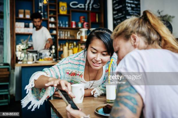 two friends looking over pictures on smartphone in cafe together - tonen stockfoto's en -beelden
