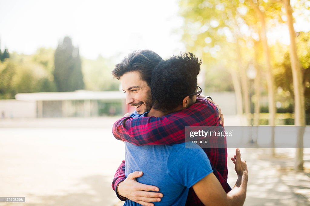 Two friends meet and hug in the streets of Barcelona. : Stock Photo
