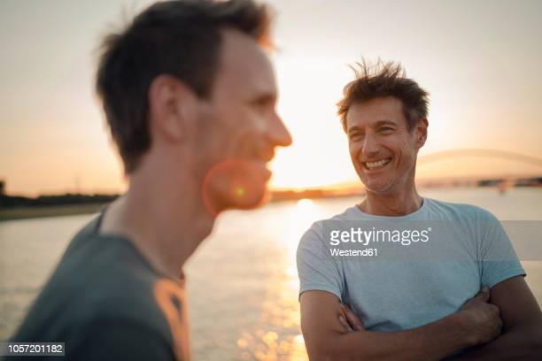 two friends meeting at sunset, spending the evening talking - mid adult men stock-fotos und bilder