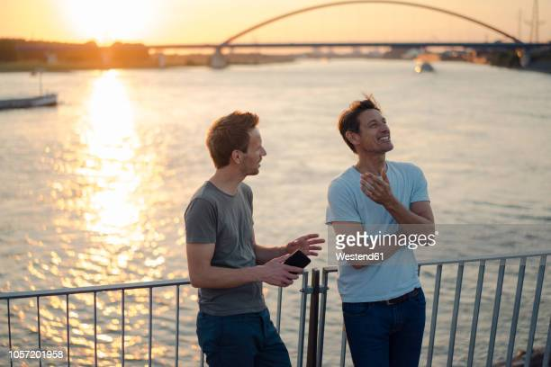 two friends meeting at sunset, spending the evening talking - männer über 30 stock-fotos und bilder