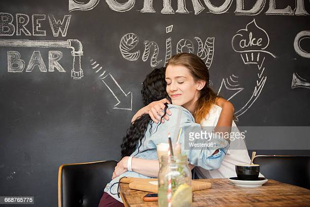 two friends meeting in cafe, embracing - amicizia tra donne foto e immagini stock