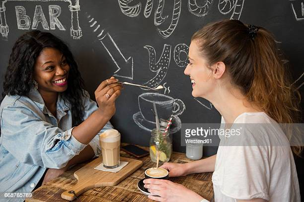 Two friends meeting in cafe, sharing coffee