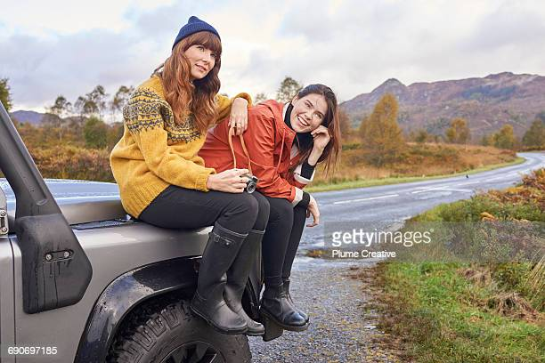 Two friends on a road trip - sat on their car