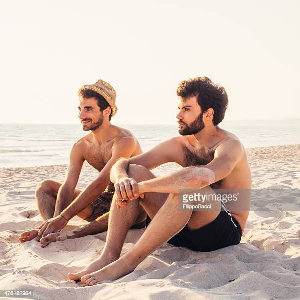 two friends on the beach together - gay men swimwear stock pictures, royalty-free photos & images