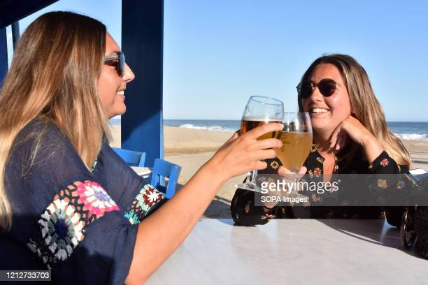Two friends on the terrace of a beachside restaurant toast to their first drink since the beginning of the confinement Having managed to pass to...