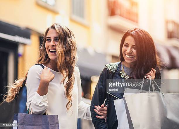Two friends ont the street with shopping bags
