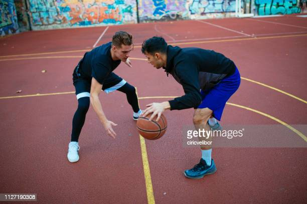 two friends playing basketball outdoors - basketball hoop stock pictures, royalty-free photos & images