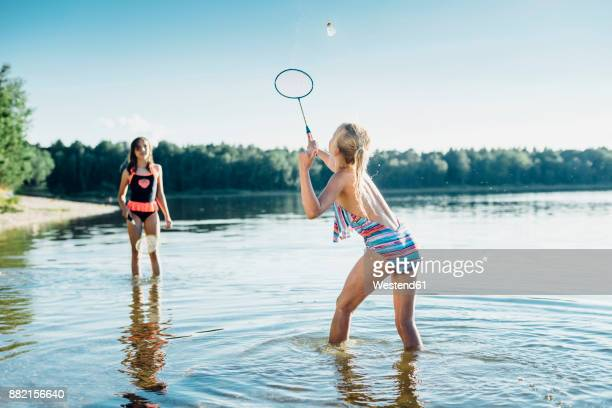 two friends playing shuttlecock at lakeshore - badminton sport stock photos and pictures
