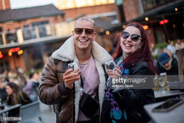 Two friends pose for a photograph in the beer garden at Dukes 92 bar on April 12, 2021 in Manchester, England. England has taken a significant step...