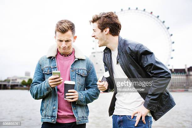 Two friends reacting to bizarre text message by the Thames