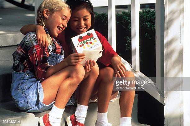 two friends reading a greeting card - altruismo foto e immagini stock