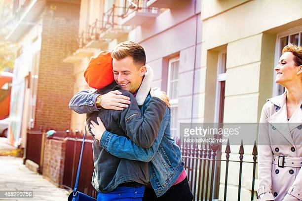 Two friends reunite on street in front of happy girlfriend