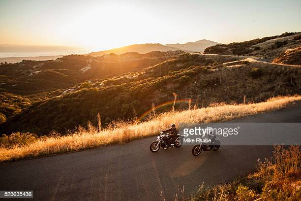 Two friends riding motorcycles together on country roads, Santa Barbara County, California, USA
