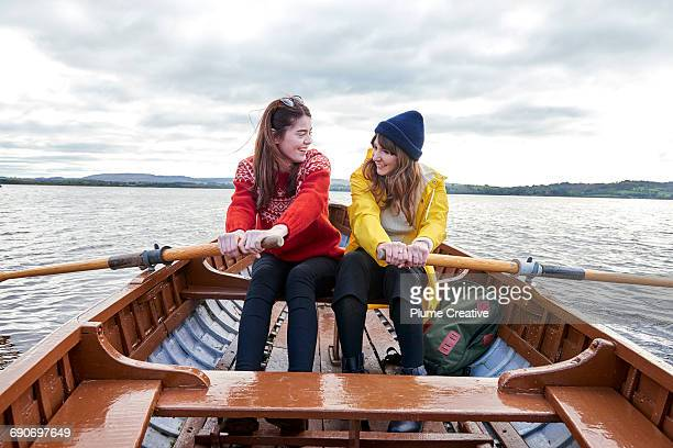 two friends rowing in a boat - female friendship stock pictures, royalty-free photos & images