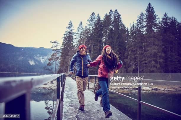 Two friends, running across bridge, Garmisch-Partenkirchen, Bavaria, Germany