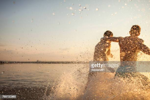 two friends running in water - lake sunset stock pictures, royalty-free photos & images