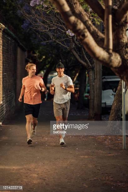 zwei freunde laufen - aktiver lebensstil stock-fotos und bilder
