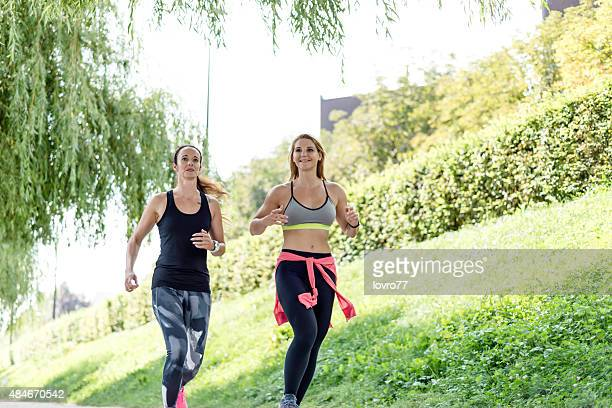 Two friends running through the park in the city