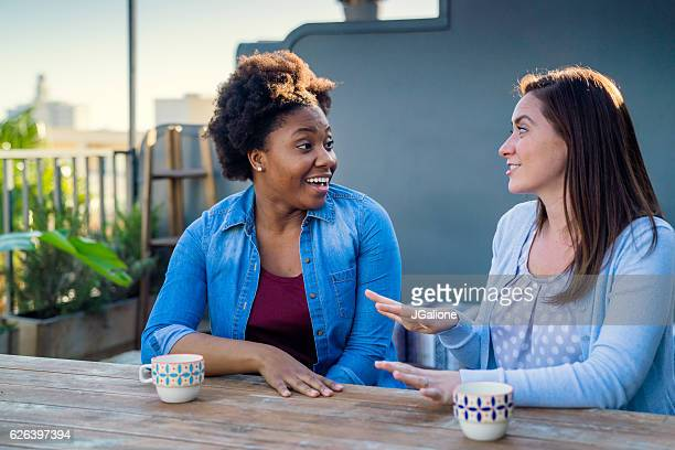 Two friends sat outside at early evening talking
