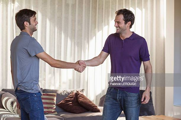 Two friends shaking hands and smiling