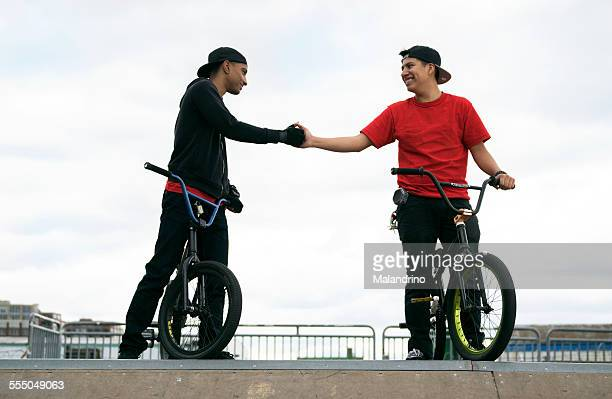 Two friends shaking hands on their BMX Bikes