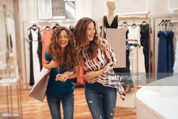two friends shopping for clothes - merchandise stock photos and pictures