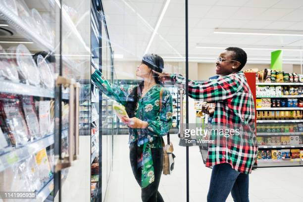 two friends shopping in supermarket - doing a favor stock pictures, royalty-free photos & images