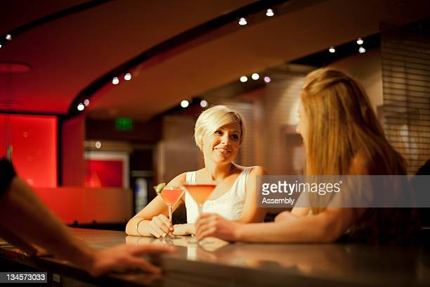 Two friends sit at a bar and talk over drinks.