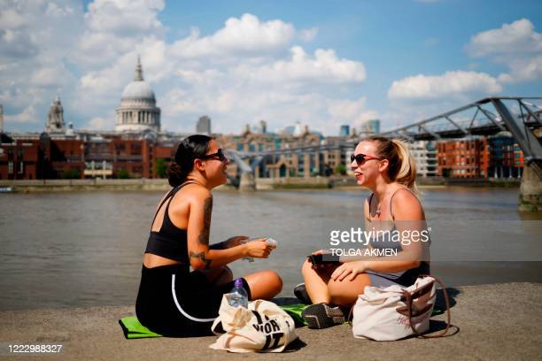 Two friends sit beside the River Thames enjoying their lunch in the sunshine in London on June 26 as temperatures are expected to again be high,...