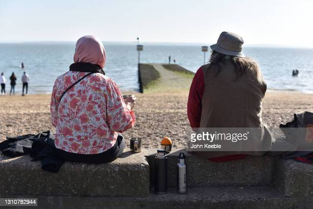 Two friends sit on the sea wall on a warm sunny Easter Sunday at Chalkwell beach on April 04, 2021 in Southend-on-Sea, England. Earlier this week,...