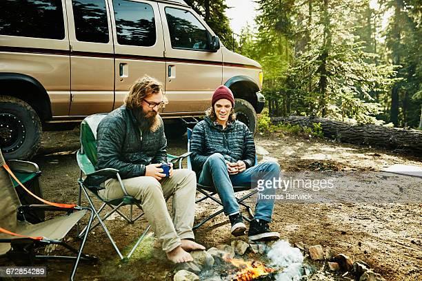 two friends sitting by campfire having coffee - landfahrzeug stock-fotos und bilder
