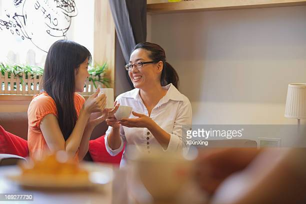two friends sitting in a coffee shop and talking - focus on background ストックフォトと画像