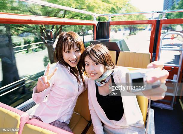 Two Friends Sitting in an Open Top Bus in Tokyo Photographing Themselves