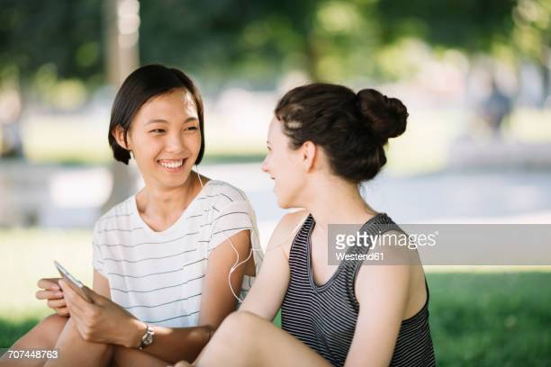 two friends sitting in city park listening music together with earphones - knees together stock photos and pictures