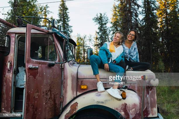 Two friends sitting on a broken truck