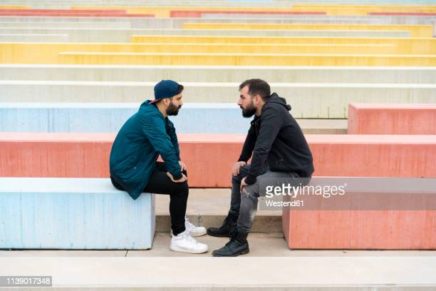 two friends sitting on benches looking at each other - angesicht zu angesicht stock-fotos und bilder