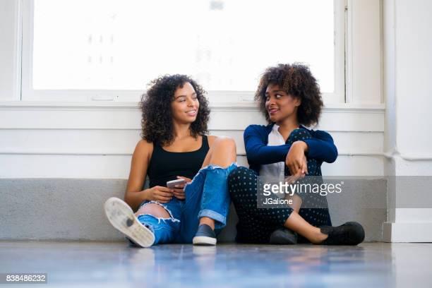 twee vrienden zittend op de vloer chatten - afro amerikaanse etniciteit stockfoto's en -beelden
